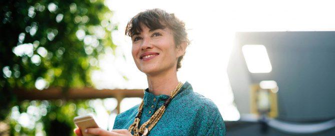 Eine Frau, die lächelnd auf Ihr Smartphone schaut