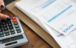 Eine Frau bearbeitet ihre Rechnungen und ist vorbereitet auf die Gesetzesänderung in 2020