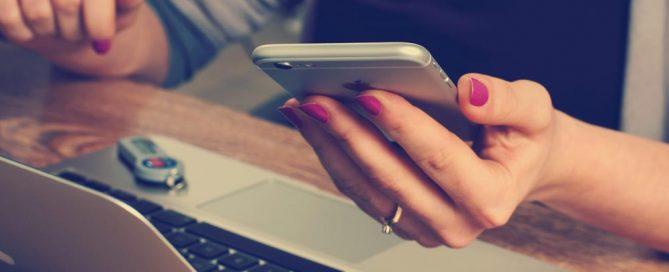 Eine Frau kontrolliert auf Ihrem Smartphone die Abrechnungen